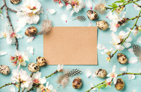 Easter background with eggs and almond flowers paper in center