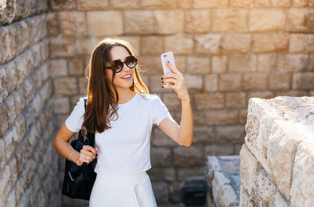 Happy young woman taking selfie