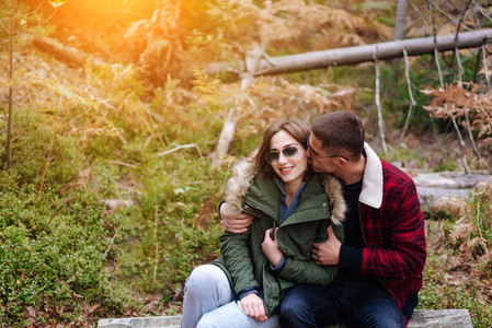 guy kisses his girlfriend in the forest