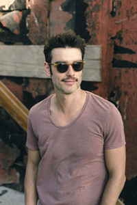 Adult stylish man in t shirt and sunglasses on street