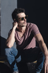 Adult stylish man in t shirt and sunglasses seated on street
