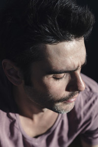 Headshot of pensive stylish man in t shirt seated in the street