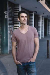 Portrait of middle aged bearded guy in pink t shirt posing on st
