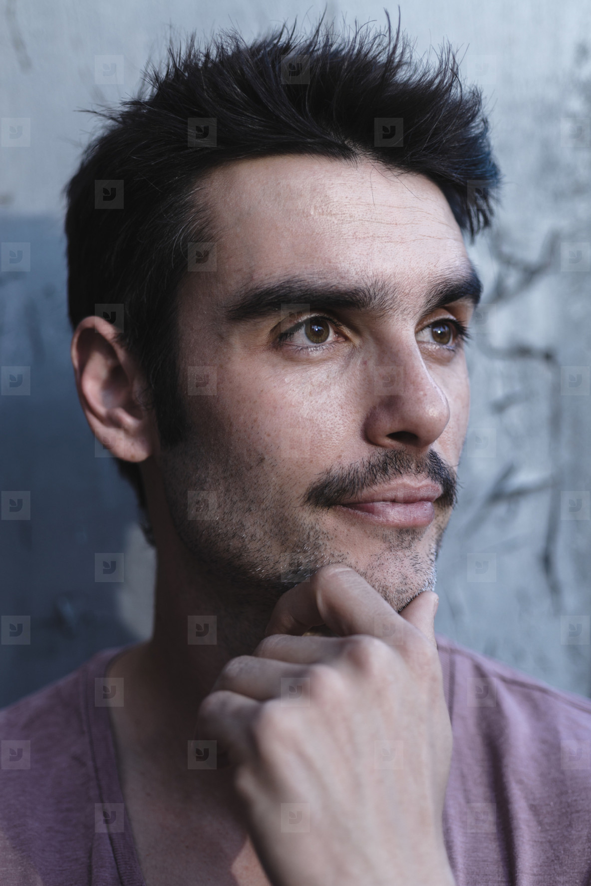 Headshot of middle aged bearded man looking pensively away in su