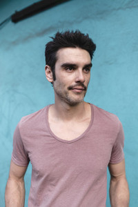 Adult bearded man wearing casual pink t shirt and standing again