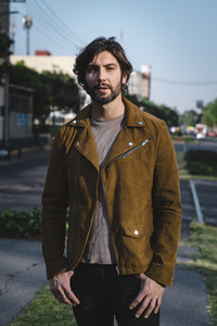 Trendy adult man in jacket on street