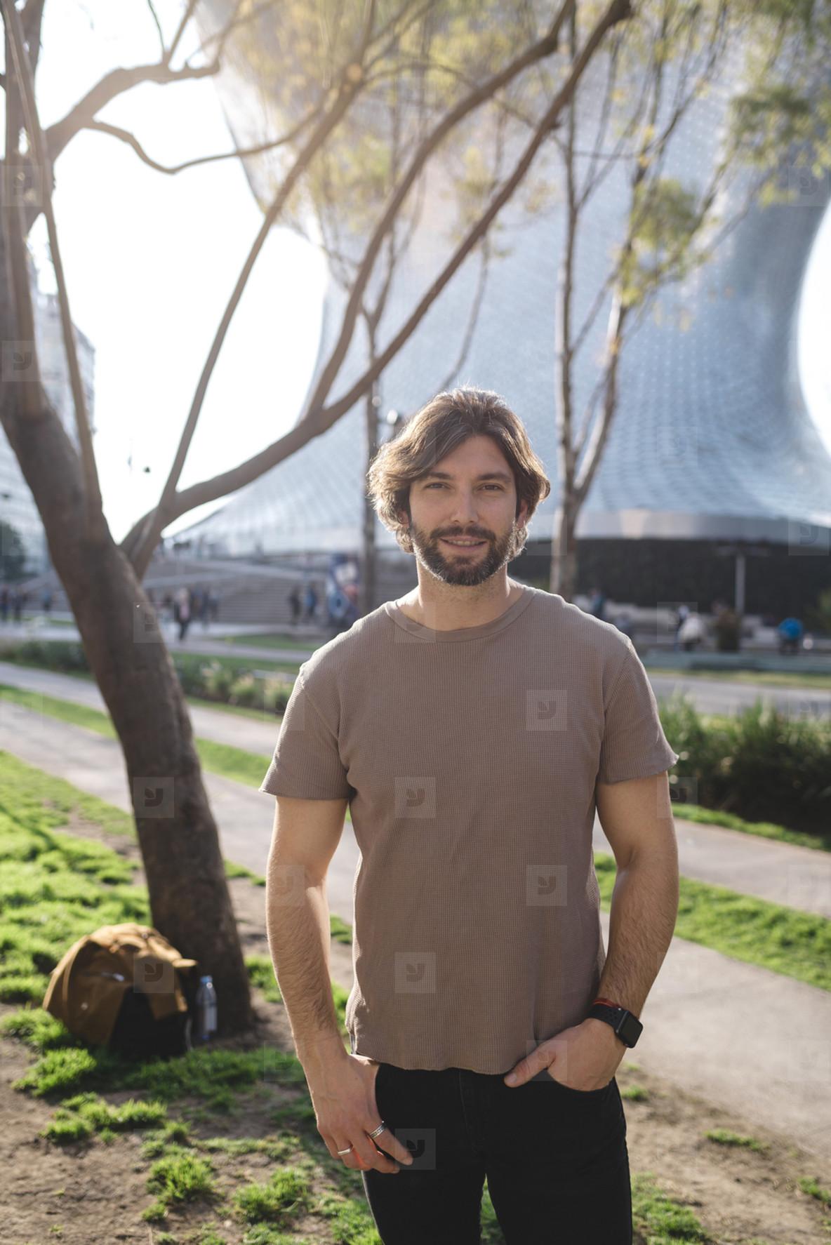 Modern bearded man posing on street