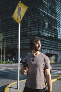 Contemporary adult man speaking on phone on street