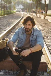 Bearded adult man speaking on phone outdoors