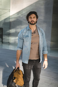 Stylish adult man standing with bag on airport