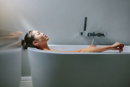 Asian female lying in bathtub