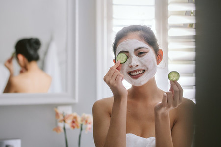 Woman with face pack in bathroom