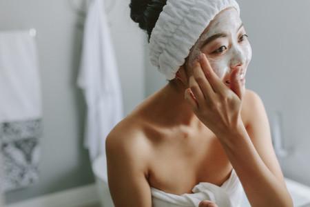 Female in applying facepack in bathroom