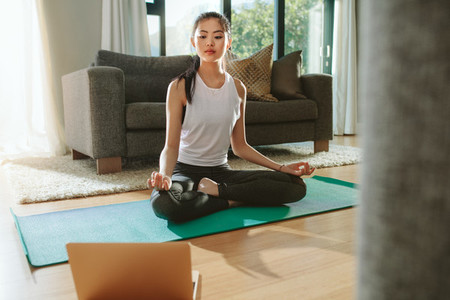 Woman doing yoga while watching instructional videos on laptop
