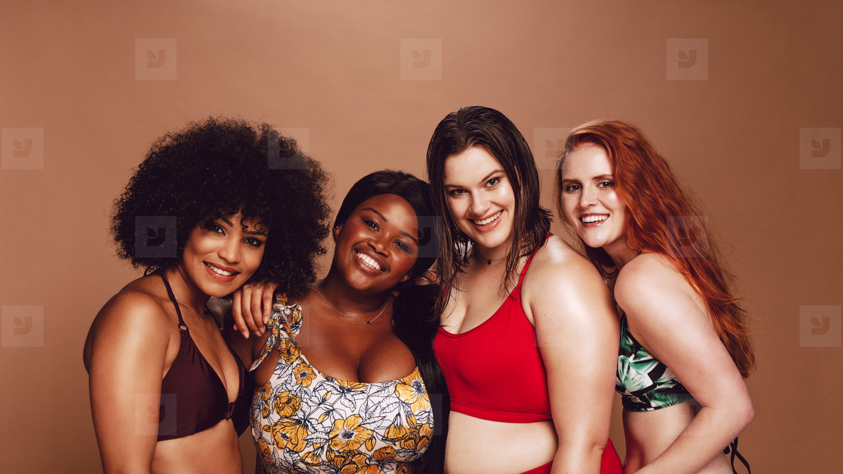Group of happy different size women in bikinis