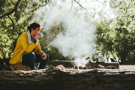 Man camping in forest sitting near a bonfire