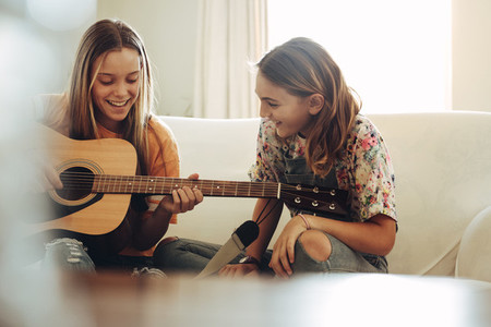 Happy girls playing guitar at home