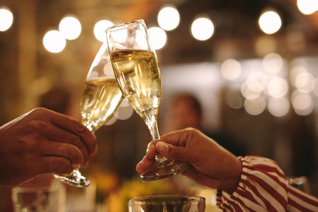 Couple toasting champagne glasses at party