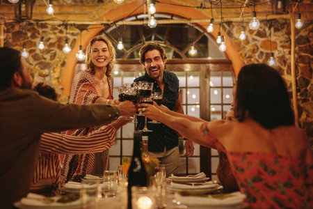 Host couple toasting drinks with guest at party