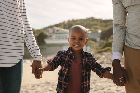 Boy walking with his parents on beach
