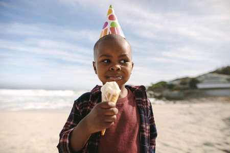 Birthday boy having ice cream on beach
