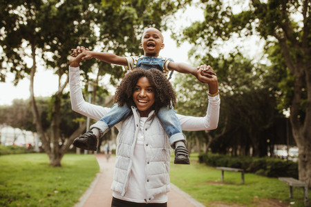 Woman giving son a piggyback ride on shoulders at park