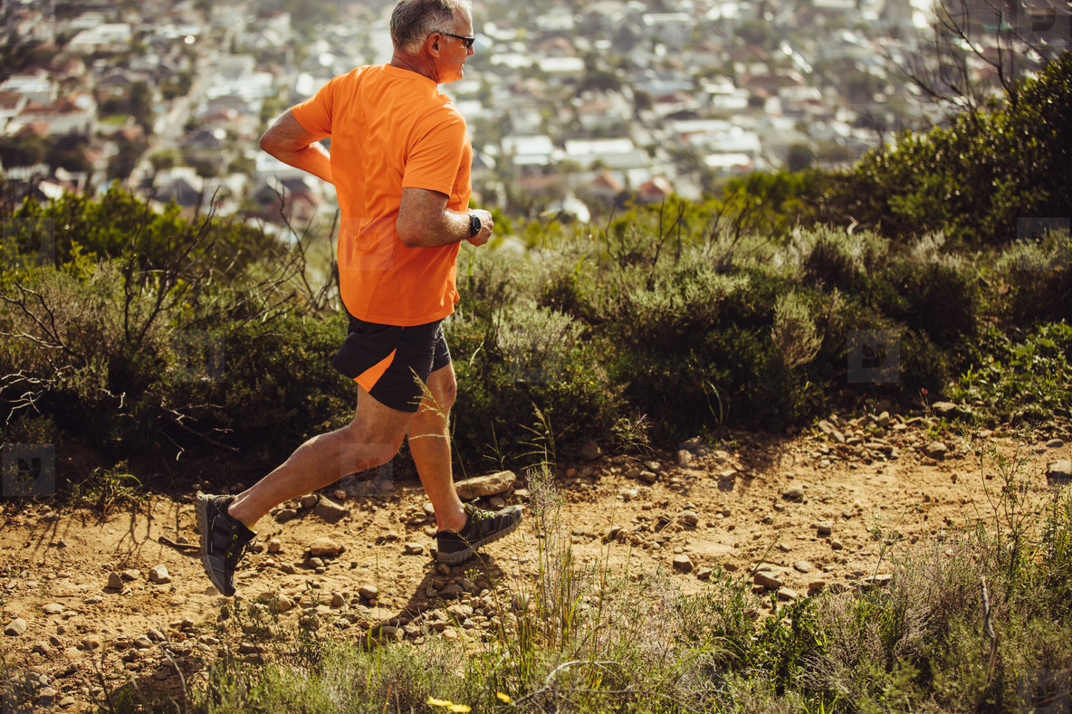 Athletic man running on a hill