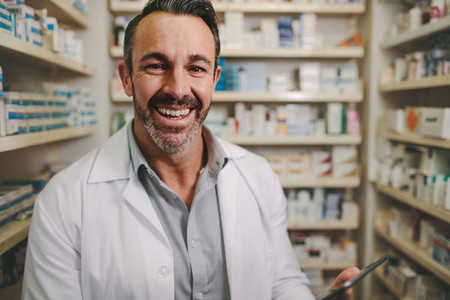 Professional male pharmacist working in medical store