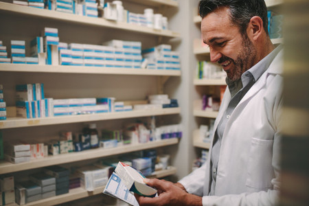 Pharmacist holding prescription and checking medicine in pharmac