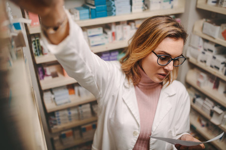 Chemist with prescription searching a medicine