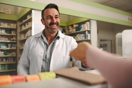 Chemist assisting customer at pharmacy store