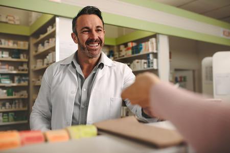 Chemist assisting customer at pharmacy store