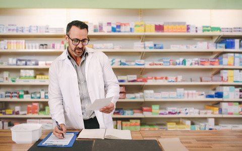 Male pharmacist writing prescription at workplace