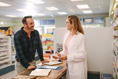Pharmacist helping customer at pharmacy