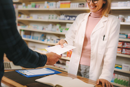 Customer giving prescription to pharmacist in pharmacy