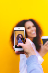 Woman photographing friend with mobile phone