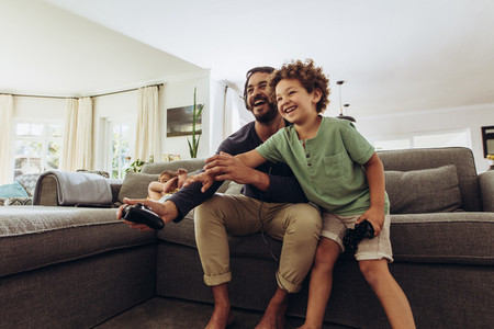 Man looking after kids at home and playing with them