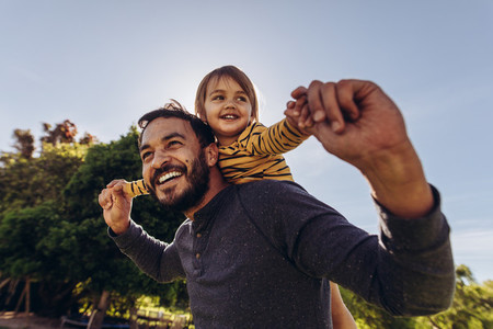 Smiling man playing with his kid outdoors