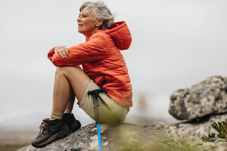 Female trekker sitting on a rock relaxing