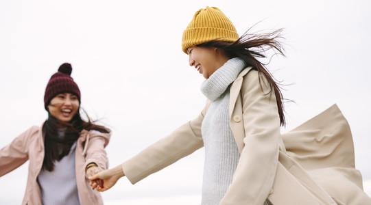 Happy asian woman in winter wear walking outdoors holding hands