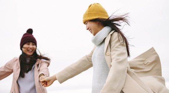 Happy asian woman in winter wear walking outdoors holding hands