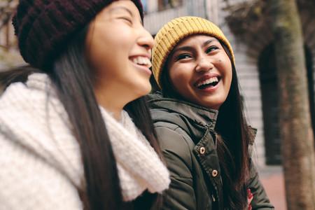 Cheerful asian women walking on street