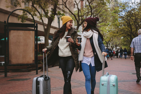 Tourist women walking on street with luggage bags