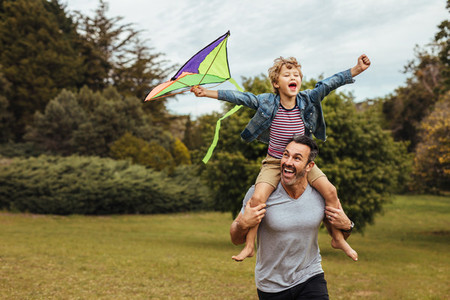 Father carrying son playing with kite in park