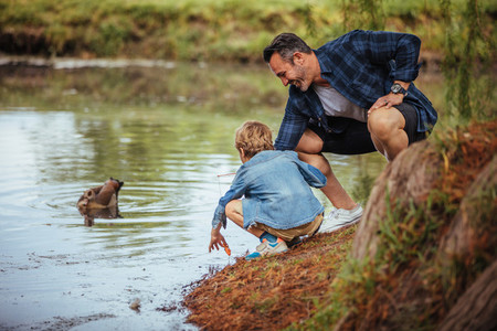 Father teaching little son fishing at pond