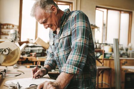 Carpenter preparing drawing for furniture parts
