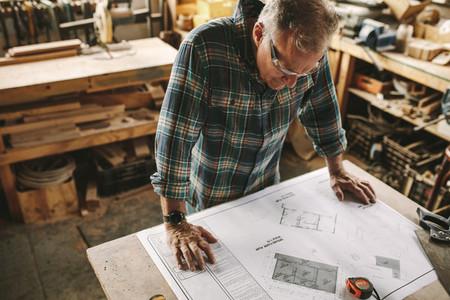 Senior carpenter studying blueprint at workshop