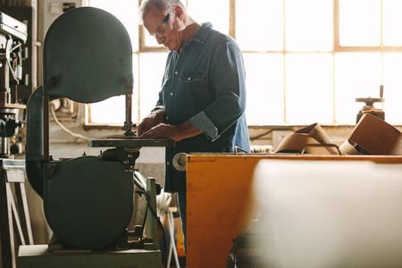Senior worker working on band saw machine