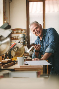 Happy senior male carpenter with phone in workshop