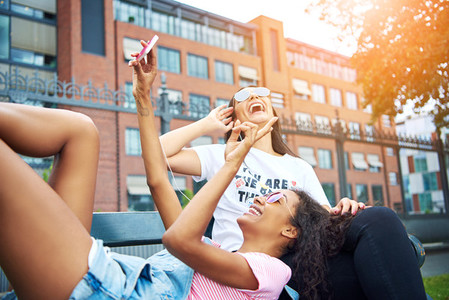 Laughing young girlfriends lying on a bench outside taking selfies